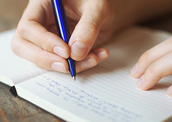 Person writing a journal entry.